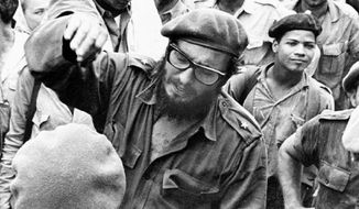 **FILE** This April 1961 photo shows Fidel Castro (center) with members of the Revolutionary Armed Forces at his base of operations at the Australia Sugar Refinery in Jaguey, near Playa Giron, during the Bay of Pigs invasion. (Associated Press)