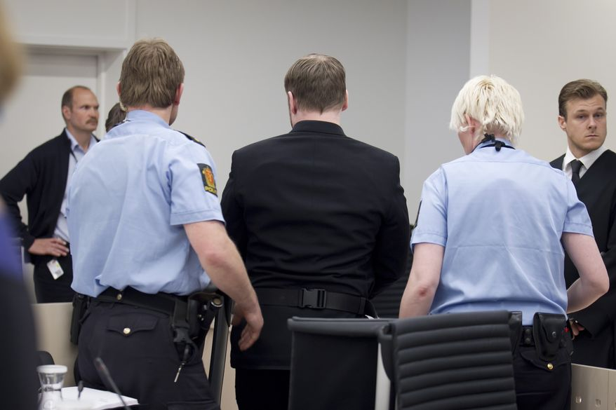 """The self-styled anti-Muslim militant Anders Behring Breivik (center) is escorted May 11, 2012, from a courtroom in Oslo by police after his trial was interrupted briefly by the brother one of his 77 victims. The brother hurled a shoe at him and yelled, """"Go to hell"""" before being escorted from the courtroom, police and witnesses said. (Associated Press/NTB scanpix)"""