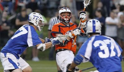 Virginia's Colin Briggs (34) passes the ball against Duke during an NCAA college lacrosse game, Friday, April 13, 2012, in Charlottesville, Va. (AP Photo/The Daily Progress, Sabrina Schaeffer)