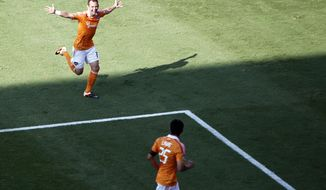 Houston Dynamo's Brad Davis, left, celebrates after scoring a goal against D.C. United as teammate Brian Ching watches during the second half Saturday, May 12, 2012, in Houston. (AP Photo/Houston Chronicle, James Nielsen)