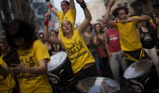 """Demonstrators play drums as they march in a protest to mark the anniversary of the beginning of the """"Indignados"""" movement in Barcelona, Spain, Saturday, May 12, 2012. Spanish activists angered by grim economic prospects planned nationwide demonstrations Saturday to mark the one-year anniversary of their protest movement that inspired similar groups in other countries. (AP Photo/Emilio Morenatti)"""