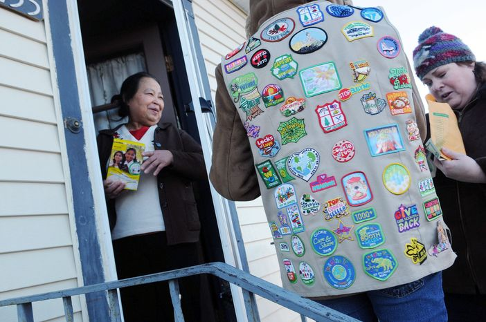 ** FILE ** A Girl Scout, wearing her vest covered in badges, sells a box of cookies to Paa Yang (left), a neighbor, in Minneapolis in 2012. (Associated Press)