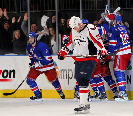 A dismayed Jason Chimera skated away as New York Rangers players celebrated a goal by Michael Del Zotto (4) in the third period of Game 7 on Saturday night. (Associated Press)