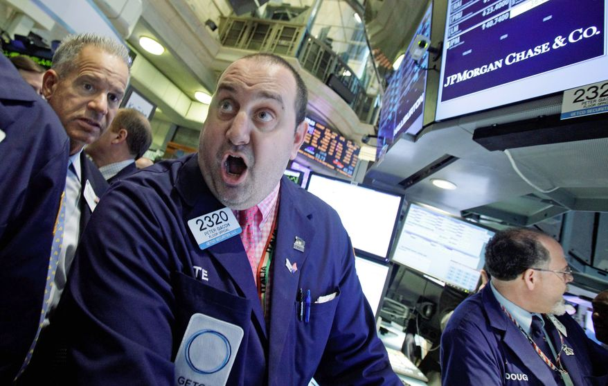 Specialist Peter Giacchi (center) calls out prices as he works at the post that handles JP Morgan Chase stock on the floor of the New York Stock Exchange, on Friday. The bank's trading loss of $2 billion will cost three high-ranking executives their jobs. (Associated Press)