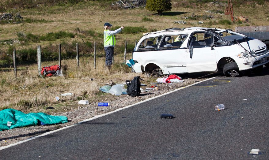 Police examine the scene of a minivan crash near Turangi, New Zealand, that killed three Boston University students and hurt five others on Saturday. The students were studying in New Zealand and were on their way to a hiking destination when the driver lost control and the van rolled over. (Associated Press)