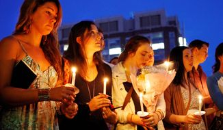 Tori Pinheiro (left) of New Bedford, Mass., the girlfriend of Austin Brashears, one of the students killed in the van crash in New Zealand, holds a candle during a vigil with others on Marsh Plaza at Boston University on Saturday after word of the fatal accident was received.