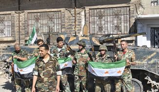 Former Syrian soldiers hold flags of the Syrian revolution as they stand in front their armored personnel carrier shortly after defecting and joining the rebels in the Khaldiyeh neighborhood in Homs province in central Syria on Saturday, May 12, 2012. (AP Photo/Fadi Zaidan)