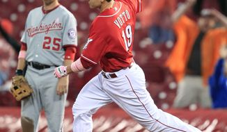 Cincinnati Reds' Joey Votto (19) rounds the bases past Washington Nationals first baseman Adam LaRoche after hitting a grand slam off relief pitcher Henry Rodriguez in the ninth inning, Sunday, May 13, 2012, in Cincinnati. Votto had three home runs as Cincinnati won 9-6. (AP Photo/Al Behrman)