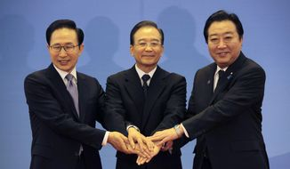 South Korean President Lee Myung-bak (left), Chinese Premier Wen Jiabao (center) and Japanese Prime Minister Yoshihiko Noda pose for photographs ahead of the fifth trilateral summit among the three nations in Beijing on Sunday, May 13, 2012. (AP Photo/Petar Kujundzic, Pool)