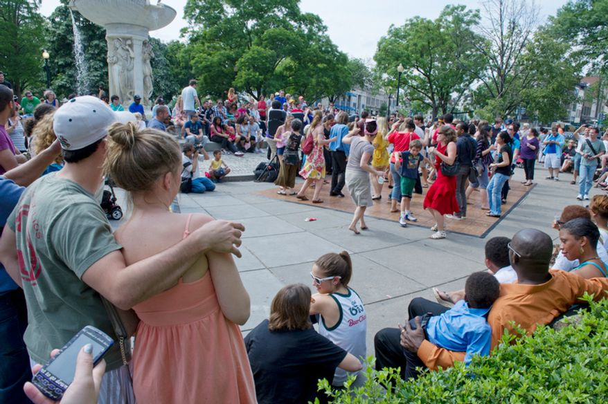 A crowd gathers at Dupont Circle both to watch and to participate in Dance in the Circle, a dance festival for all ages. Nine official dance organizations performed on the stage in front of the fountain, but in between performances the audience joined in.  (Barbara L. Salisbury/The Washington Times)