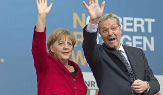 ** FILE ** German Chancellor Angela Merkel and Norbert Roettgen, a candidate of the conservative Christian Democratic Union party, wave during a campaign rally in Gelsenkirchen, Germany, on Wednesday, May 9, 2012, ahead of elections in the populous German state of North Rhine-Westphalia. (AP Photo/Martin Meissner)