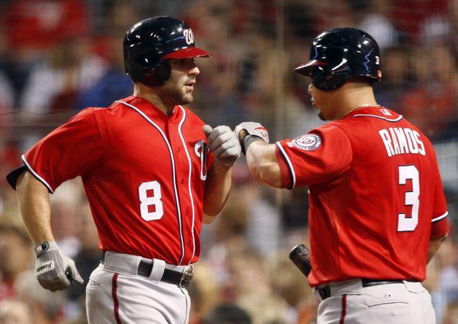 Washington Nationals second baseman Danny Espinosa (8) is congratulated by Wilson Ramos (3) after Espinosa hit a solo home run off Cincinnati Reds relief pitcher Jose Arredondo in the sixth inning Saturday, May 12, 2012, in Cincinnati. The Nationals won 2-1. (AP Photo/Al Behrman)