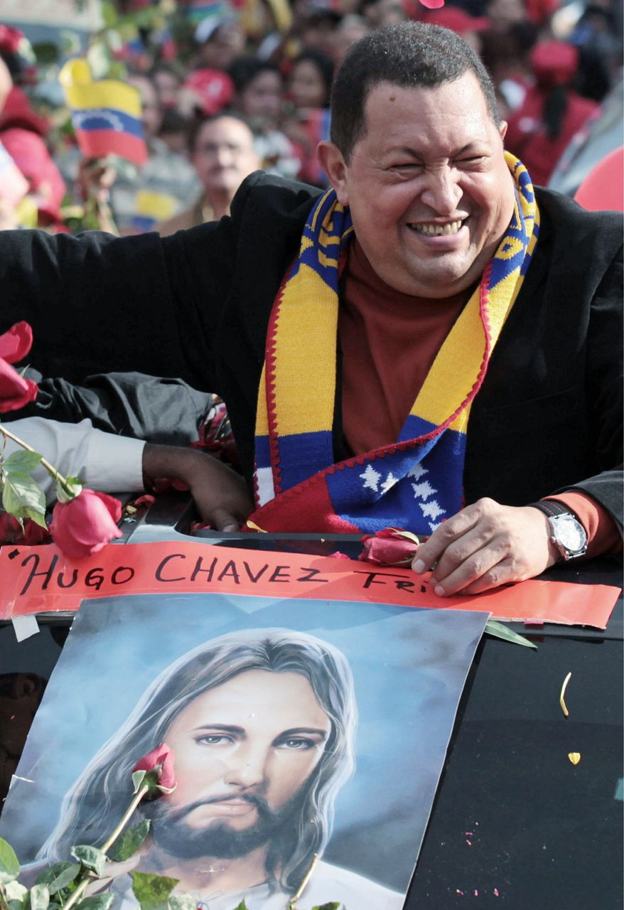 Venezuelan President Hugo Chavez greets well-wishers on Feb. 24 as he prepares to return to Cuba for cancer surgery. The poster is of Jesus, to whom he is praying for a miracle. (Associated Press)