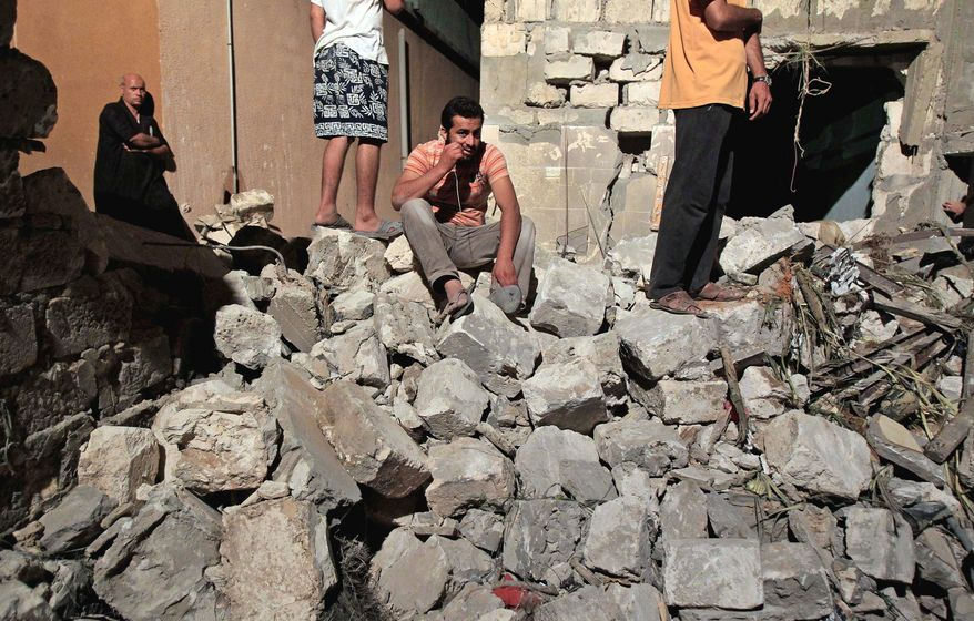 A Libyan man sits on debris from a damaged residential building on the outskirts of Tripoli, Libya, in June. Human Rights Watch is calling on NATO to provide compensation for Libyans who lost loved ones or had property damaged in airstrikes during the bombing campaign that helped rebels oust former leader Moammar Gadhafi. (Associated Press)