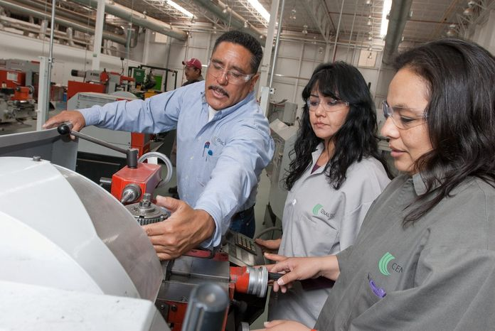 Instructor Hipolito Correa shows students Isabel Lugo (right) and Luisa Elizondo how to operate a lathe at Cenaltec, an aerospace-industry training center in Chihuahua City, Mexico, set up by state and federal governments in collaboration with local businesses. (Keith Dannemiller/Special to The Washington Times)