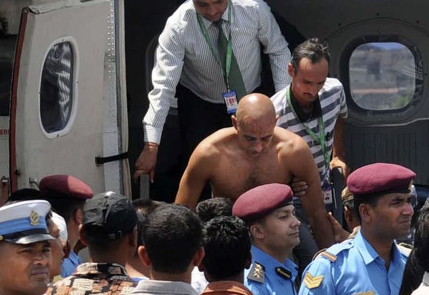 Andreas Rasch (center), a Dane who was one of six survivors of a plane crash in the Himalayas, is taken for treatment in the nearby city of Pokhara, Nepal, on Monday, May 14, 2012. (AP Photo/Krishnamani Baral)