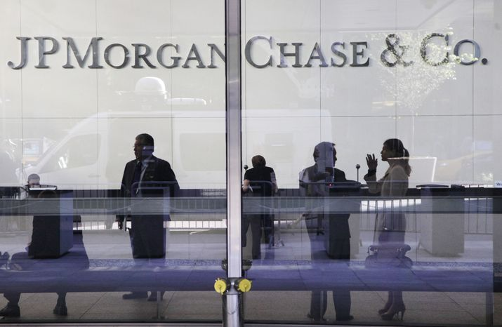 People are pictured in the lobby of JPMorgan Chase's headquarters in New York on Friday, May 11, 2012. (AP Photo/Mark Lennihan)