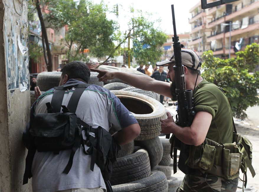 A Sunni gunman (right) points toward a possible target during clashes in the northern port city of Tripoli, Lebanon, on Monday May 14, 2012. (AP Photo/Hussein Malla)