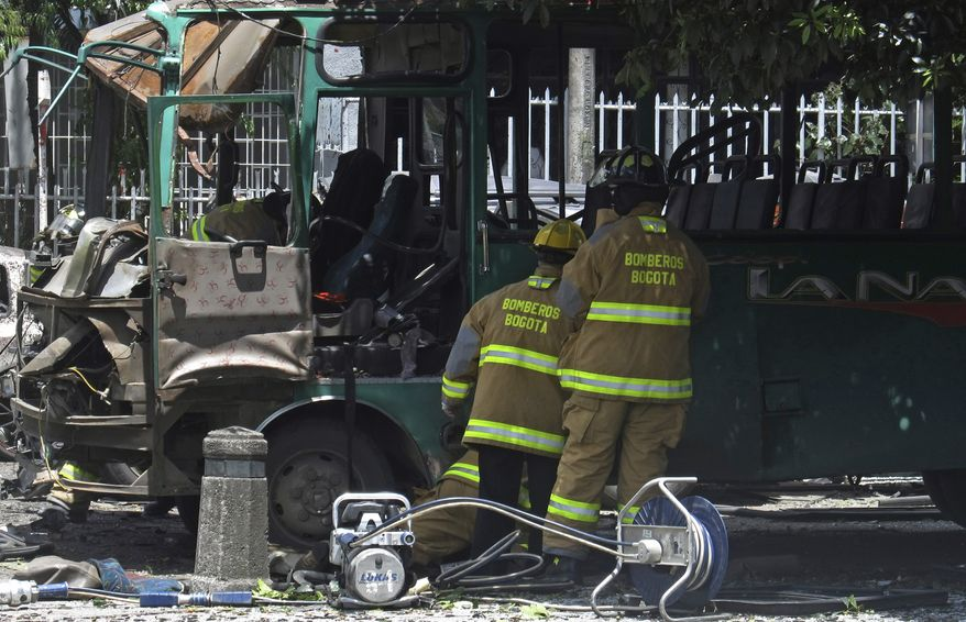 ** FILE ** Firefighters inspect a damaged bus at the scene of a bomb attack that targeted a former Colombian interior minister in Bogota, Colombia, on Tuesday, May 15, 2012. The blast killed two people and injured at least 19 others. (AP Photo/Ricardo Mazalan)