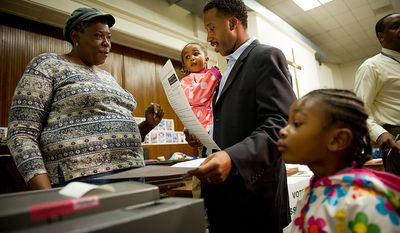 Volunteer poll worker Linda Johnson, left, helps Kenyan McDuffie, center, a candidate to replace Harry Thomas for Ward 5 city councilmember, cast his vote in the special election with his two daughters Kesi, 5, right, and Jozi, 2, second from left, at Mt. Bethel Baptist Church on Rhode Island Avenue in northwest, Washington, D.C., Tuesday, May 15, 2012 (Andrew Harnik/The Washington Times)