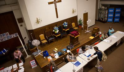 Anna Taylor, bottom right, signs in at the Mt. Bethel Baptist Church voting station on Rhode Island Avenue in northwest to cast her vote in a special election to replace Harry Thomas for Ward 5 city councilmember, Washington, D.C., Tuesday, May 15, 2012 (Andrew Harnik/The Washington Times)