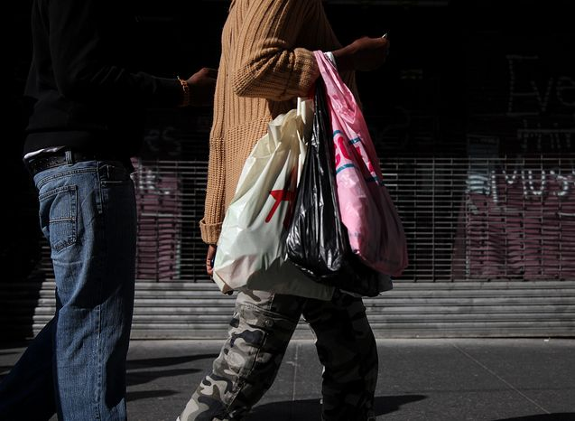 Shoppers carry their purchases along 33rd Street in New York on Sunday, May 6, 2012. (AP Photo/CX Matiash)