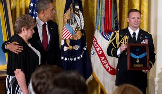 A military aid holds the Medal of Honor for President Obama to award posthumously to Rose Mary Sabo-Brown, widow of Army Spc. Leslie H. Sabo Jr., on Wednesday. Sabo died protecting his comrades in Cambodia during the Vietnam War in 1970. (Associated Press)