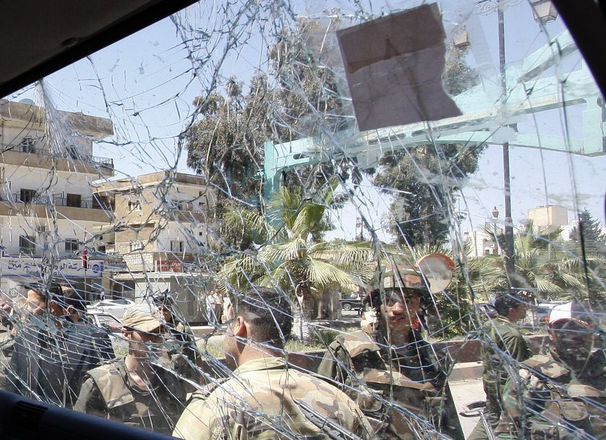 ** FILE ** Syrian soldiers are seen through the damaged window of a military truck that was hit by a roadside bomb in Daraa, Syria, on Wednesday, May 9, 2012. The blast occurred just seconds after a team of U.N. observers passed by. (AP Photo/Muzaffar Salman)