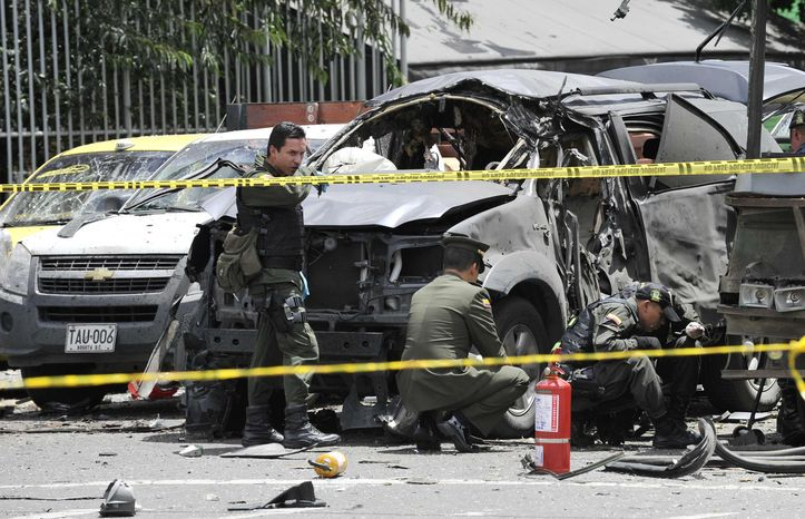 Police inspect the scene after a bomb exploded in Bogota, Colombia, Tuesday, May 15, 2012. (AP Photo/Carlos Julio Martinez)