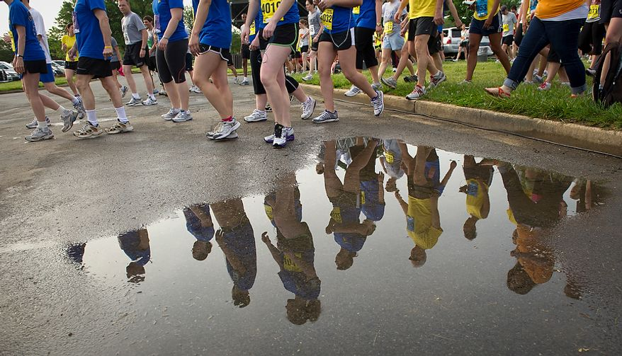 Runners are seen in a puddle from previous rains as they make their way to the starting line for the ACLI Capital Challenge at Anacostia Park in Washington, D.C., Wednesday, May 16, 2012. This is the 31st running of the three-mile race where members of Congress, national media outlets and locals take part in this fundraising event in the early morning hours along the water of the Anacostia River.  (Rod Lamkey Jr/The Washington Times)