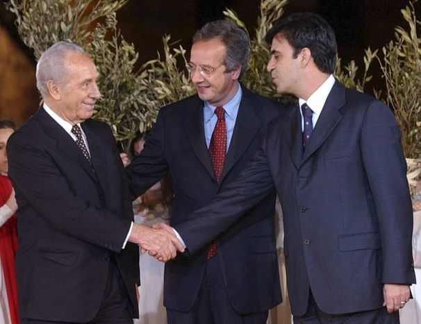 **FILE** Palestinian leader Yasser Arafat's economic adviser Mohammed Rashid (right) and then-Israeli Foreign Minister Shimon Peres (left) shake hands May 11, 2002, as Rome's mayor Walter Veltroni looks on at a ceremony before the start of a concert in Rome's Colosseum. (Associated Press)