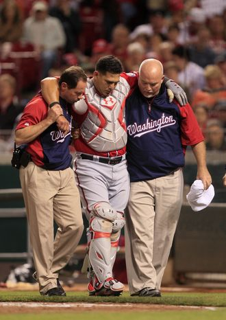 Washington Nationals catcher Wilson Ramos is helped after he was injured during game against the Cincinnati Reds on Saturday, May 12, 2012 in Cincinnati. Ramos ended up tearing his ACL in his right knee attempting to field a passed ball. (AP Photo/Al Behrman)