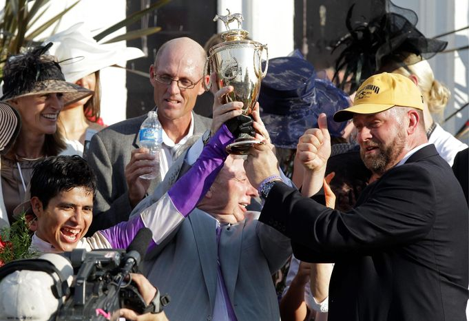 Jockey Mario Gutierrez , left, owner J. Paul Reddam , middle, and trainer Doug O'Neill hold the trophy after I'll Have Another won the 138th Kentucky Derby horse race at Churchill Downs on Saturday, May 5, 2012, in Louisville, Ky. (AP Photo/Mark Humphrey)