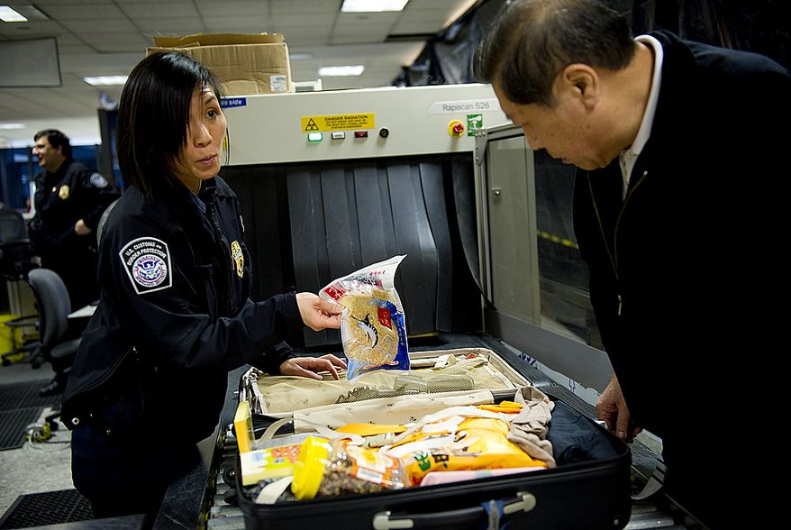 Customs and Border Protection Officer Rebecca Rhinehart questions a passenger about an item found in his suitcase at Washington Dulles International Airport on Thursday, Jan. 19, 2012. CBP throws away on average 240 pounds of seized goods daily. The items must be incinerated at 1,600 degrees for four hours. This line of defense protects America from exposure to illnesses and epidemics brought on by foodstuffs, insects and the like from other countries. (Barbara L. Salisbury/The Washington Times)