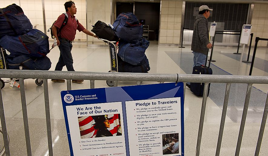 Passengers arriving at Washington Dulles International Airport in this Thursday, Jan. 19, 2012, file photo, walk past a U.S. Customs and Border Protection sign. (Barbara L. Salisbury/The Washington Times) ** FILE **