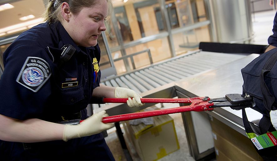 Officer Valerie Woo uses a bolt cutter to remove a lock from a suitcase that must be opened for inspection at the Agriculture screening section of Customs at Washington Dulles International Airport on Thursday, Feb. 16, 2012. Bolt cutters, knives and magnifying glasses are all common accoutrements for the officers. (The Washington Times) **FILE**