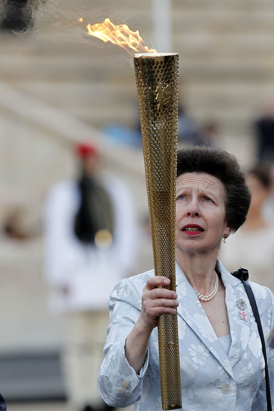 Princess Anne of Britain holds the torch with the Olympic Flame during the handover ceremony of the Olympic Flame in Panathenian stadium in Athens on Thursday, May 17, 2012. The torch begins its 70-day journey to arrive at the opening ceremony of the London 2012 Olympics, from the Greek capital, to cover about 8,000-mile (12,875-kilometer) on its progress over many parts of England to start the games. (AP Photo/Petros Giannakouris)