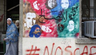 "**FILE** Two women walk Dec. 20, 2011, next to a mural depicting the faces of some of the people killed before and after the revolution at Tahrir Square in Cairo, Egypt. Arabic writing at center reads ""No conciliation."" The colorful graffiti splashed over buildings is a reminder of the revolutionary fervor that was centered in Tahrir Square. (Associated Press)"
