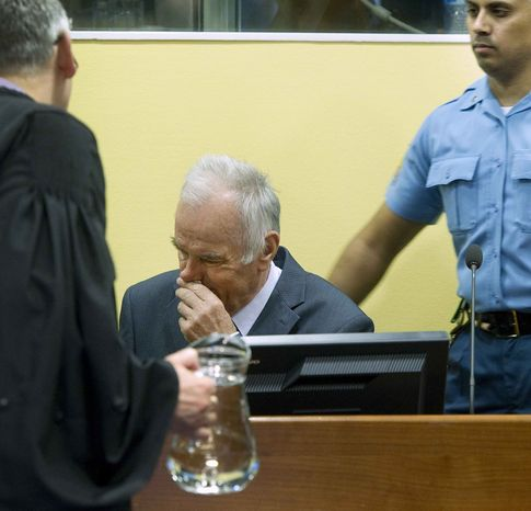 Former Bosnian Serb military commander Gen. Ratko Mladic, center, a U.N. security guard, right, and member of his defense, left, are seen at the start of his trial at the Yugoslav war crimes tribunal in The Hague, Netherlands, Wednesday, May 16, 2012. (AP Photo/Toussaint Kluiters, Pool)