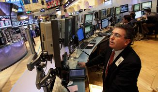 **FILE** Trader John Bishop works May 7, 2012, on the floor of the New York Stock Exchange. (Associated Press)