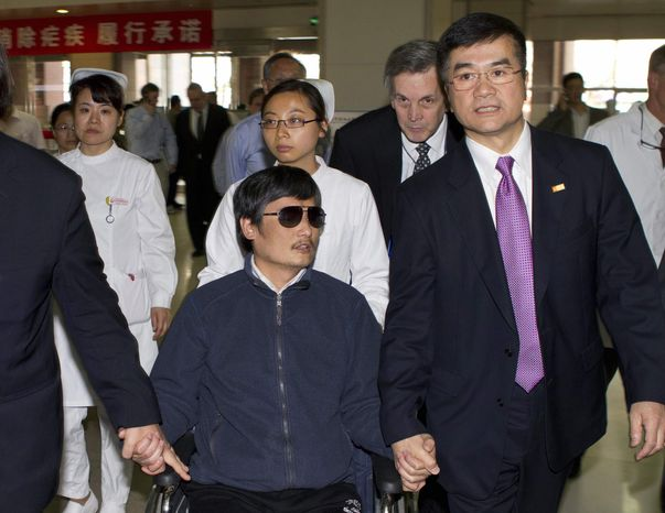 ** FILE ** In this file photo taken Wednesday, May 2, 2012, and released by the U.S. Embassy Beijing Press Office, blind activist Chen Guangcheng, center, holds hands with U.S. Ambassador to China, Gary Locke, at a hospital in Beijing. (AP Photo/U.S. Embassy Beijing Press Office, File)