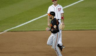 Baltimore Orioles' Nick Markakis, front, rounds the bases after hitting the go-ahead home run in the 11th inning, as Washington Nationals third baseman Ryan Zimmerman looks Friday, May 18, 2012, in Washington. The Orioles won 2-1 in 11 innings. (AP Photo/Nick Wass)