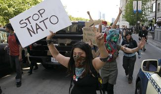 Protesters block traffic on Michigan Avenue as they march through the city during a demonstration Friday, May 18, 2012, ahead of this weekends' NATO summit in Chicago. (AP Photo/Charles Rex Arbogast)