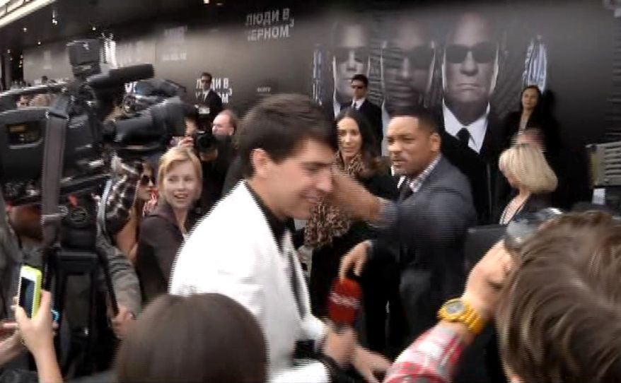 "In this video image taken from AP video U.S. actor Will Smith, center right, slaps reporter Vitalii Sediuk, white suit, from the Ukrainian television channel 1+1, on the red carpet before the premiere of ""Men in Black III"" Friday, May 18, 2012 in Moscow. (AP Photo via AP video)"