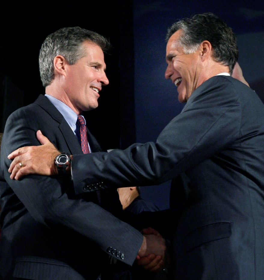 **FILE** Former Massachusetts Gov. Mitt Romney (right) introduces and congratulates Sen.-elect Scott P. Brown, Massachusetts Republican, at his Boston victory party on Jan. 19, 2010, after he won the seat vacated by Sen. Edward M. Kennedy. (Associated Press)