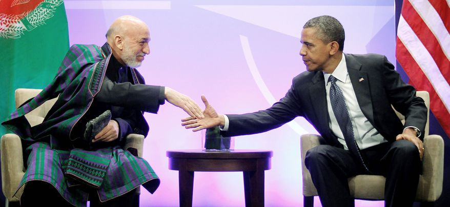 """President Obama shakes hands with Afghan President Hamid Karzai during their meeting at the NATO summit in Chicago on Sunday. Mr. Karzai thanked Americans for the help their """"taxpayers' money"""" has done in Afghanistan. (Associated Press)"""