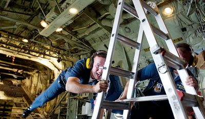 """AE2 Mark Hatfield, U.S. Navy, hangs on to a ladder while achieving weightlessness in the back of """"Fat Ernie,"""" the Blue Navy support plane, during a flight at the Joint Service Open House & Air Show Sunday. (Barbara L. Salisbury/The Washington Times)"""