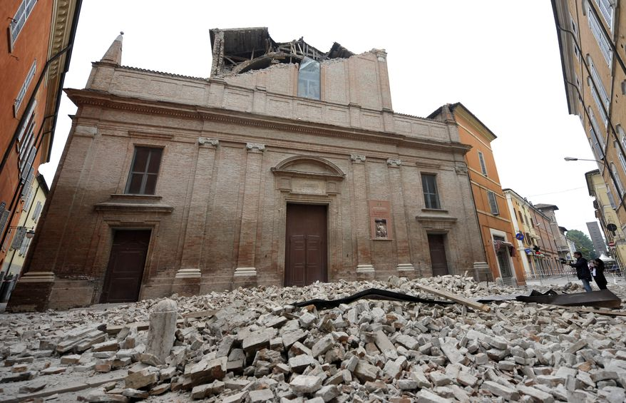 Debris from a collapsed church blocks a street in Finale Emilia, some 37 miles east of Bologna, Italy, after the region was hit a quake early Sunday, May 20, 2012. (AP Photo/Marco Vasini)