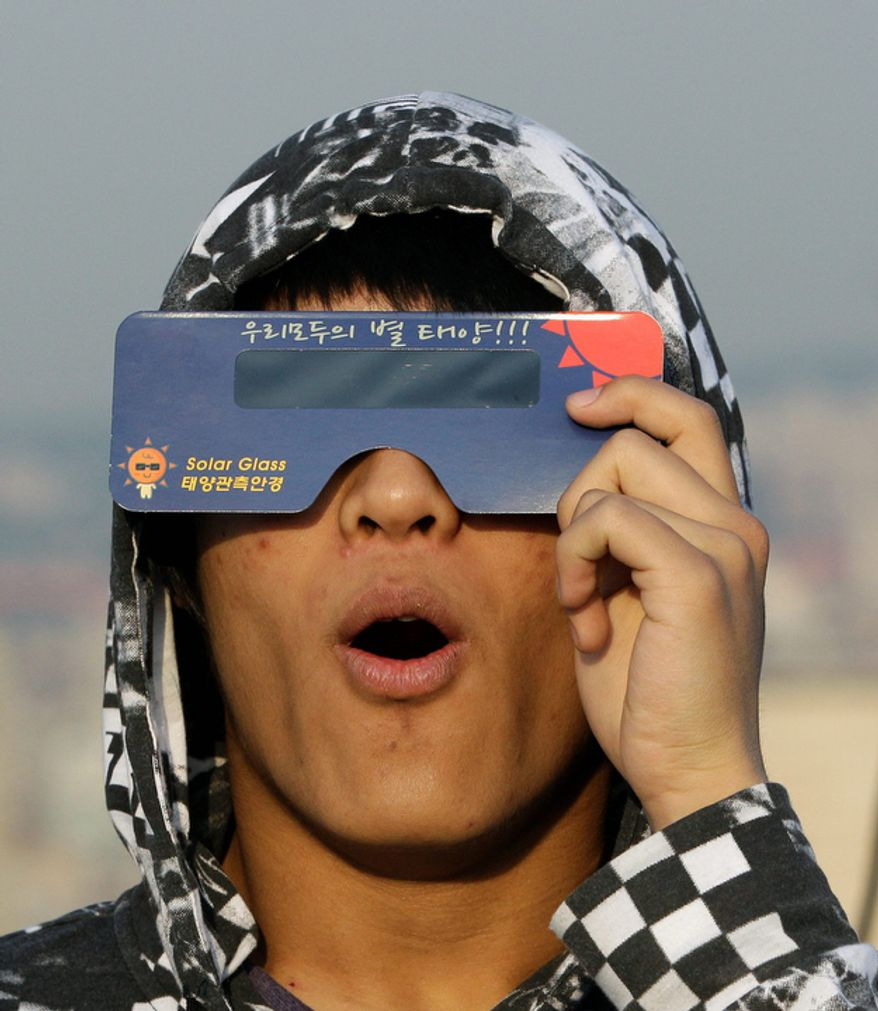 """A South Korean astronomy student uses special sunglasses to observe an annular solar eclipse in Seoul, South Korea. Millions of Asians watched as a rare """"ring of fire"""" eclipse crossed their skies early Monday.  (AP Photo/Lee Jin-man)"""
