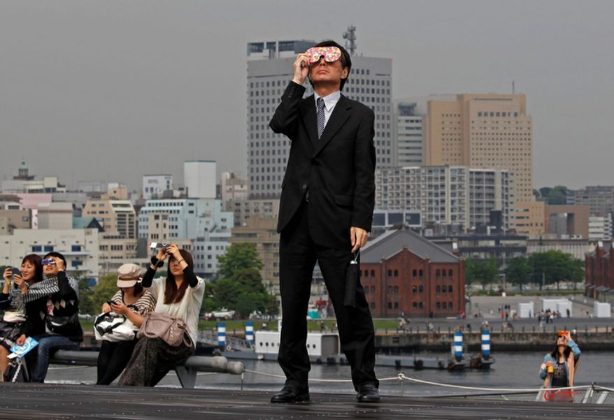 A business man watches an annular solar eclipse at a waterfront park in Yokohama, near Tokyo.  The annular eclipse, in which the moon passes in front of the sun leaving only a golden ring around its edges, was visible to wide areas across the continent. (AP Photo/Shuji Kajiyama)